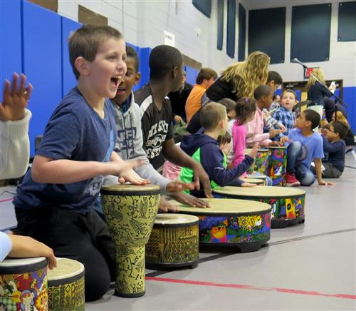 A long line of children hitting bongo drums
