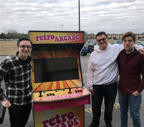 "A group of boys stand beside an arcade cabinet that says ""Retro Arcade"" on it."