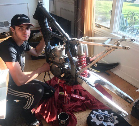 A student stands with a motorcycle in his living room that he is repairing for a project