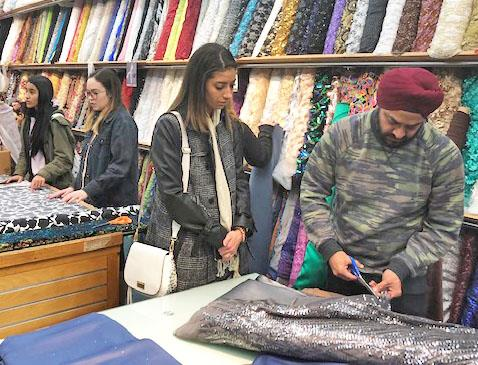 Student watches as fabric is cut