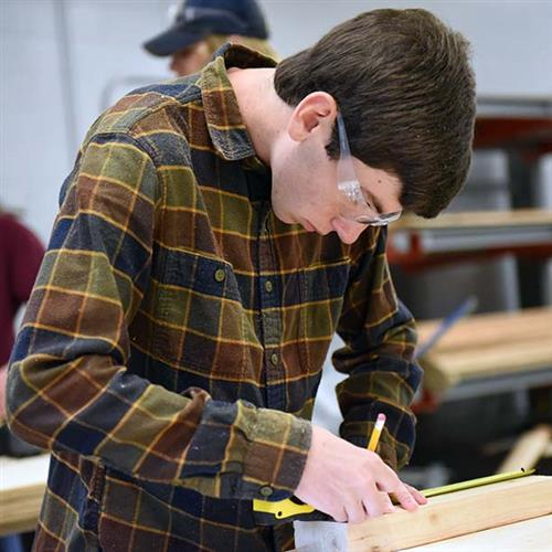 A picture of a man in a plaid shirt, wearing safety glasses, marking a small piece of wood with