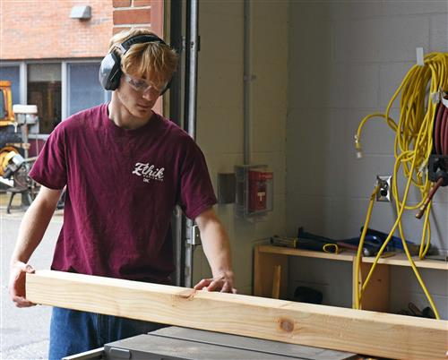 A boy wearing a red shirt, earmuffs and safety glasses cuts a piece of wood on a table saw