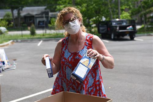 A woman wearing a face mask appears to be smiling as she puts two boxes of spaghetti into a food drive box