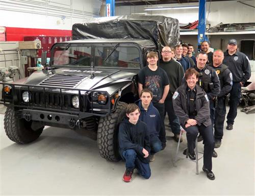 Students and police gather around completed Humvee project.