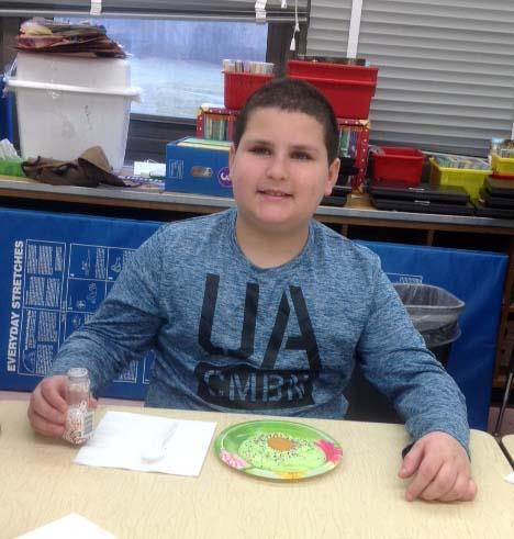 A male student  added rainbow sprinkles to his green eggs.