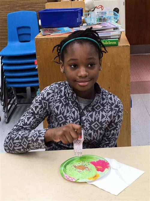 A student adds rainbow sprinkles to the green eggs.