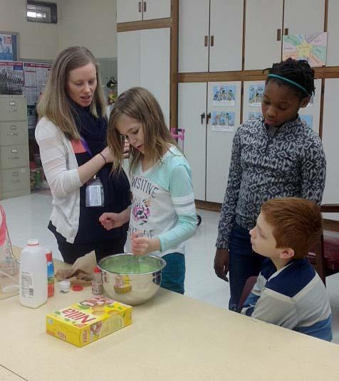 A student takes a turn stirring the ingredients together.