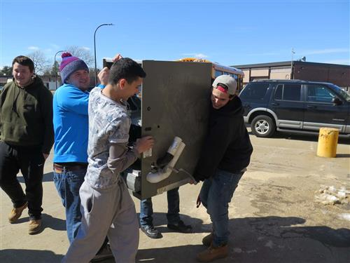 Students carry a donated piece of equipment into the building.