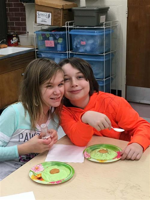 Two students enjoy green eggs made with vanilla pudding.